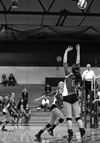 Courtney Higlin setting up sophomore middle hitter Emily Anderson to power it down.