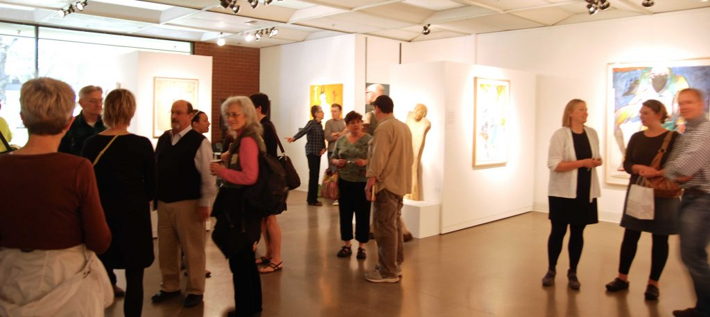 Faculty and students viewing Rick Bartow's art.